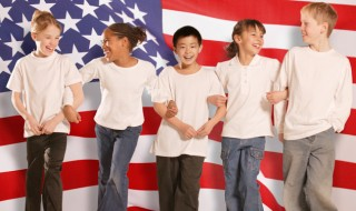 Smiling children standing arm-in-arm in front of American flag.