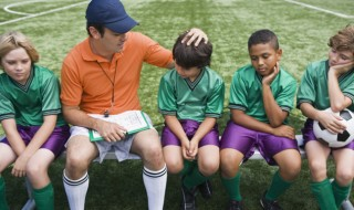 A soccer coach sits on a bench with the disappointed-looking boys on his team and encourages them.