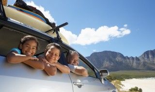 A smiling family in a car taking a road trip to the mountains.