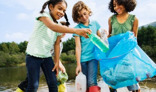 Three girls picking up plastic bottle litter from a pond.