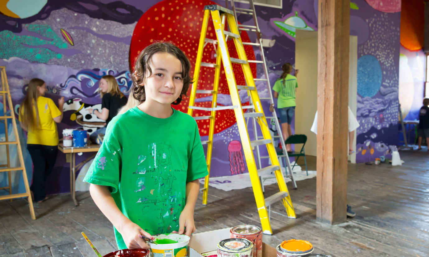 A smiling boy holding paint and looking at the camera as students paint a mural together behind him.