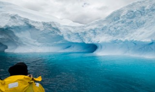 View of a man looking at an iceberg in a bright blue sea in Antarctica.