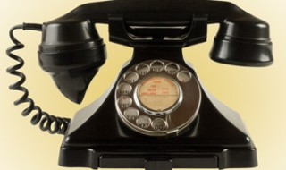 An old-fashioned black rotary phone from the 1950s.