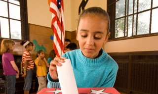 A girl placing a ballot into a ballot box during a school election.