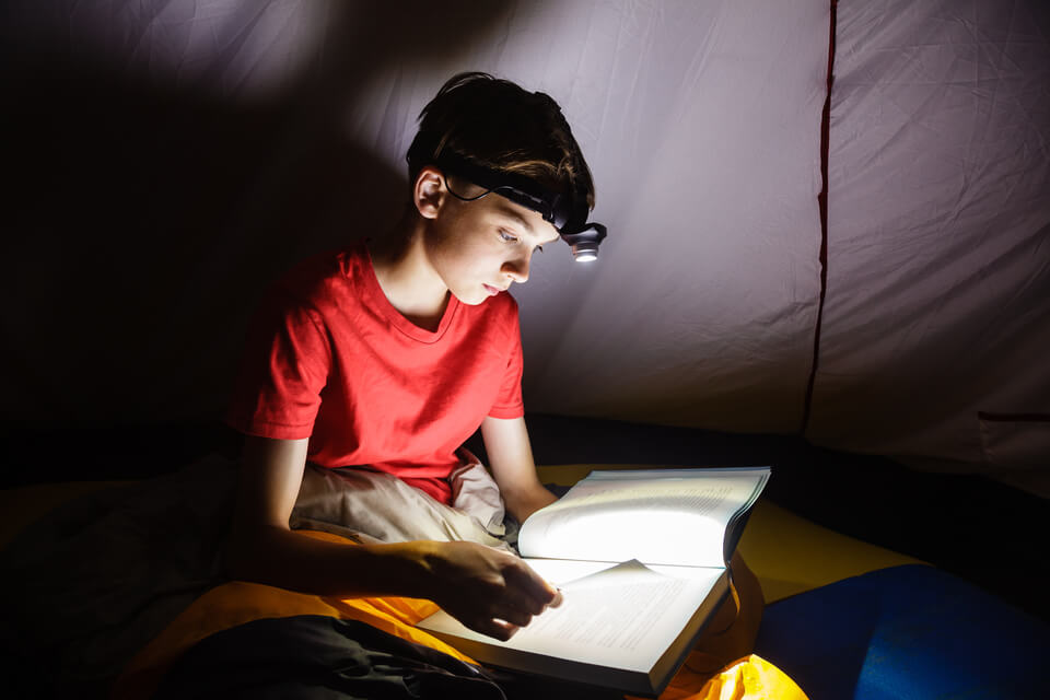 Boy using a flashlight to read at night