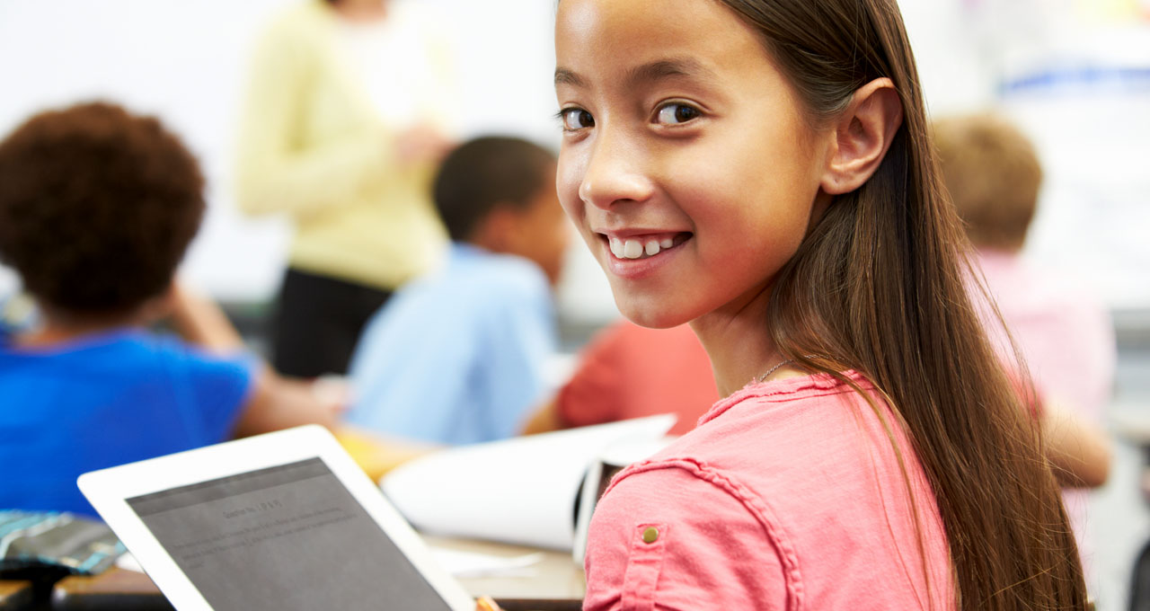 A smiling girl using a digital tablet in the classroom.