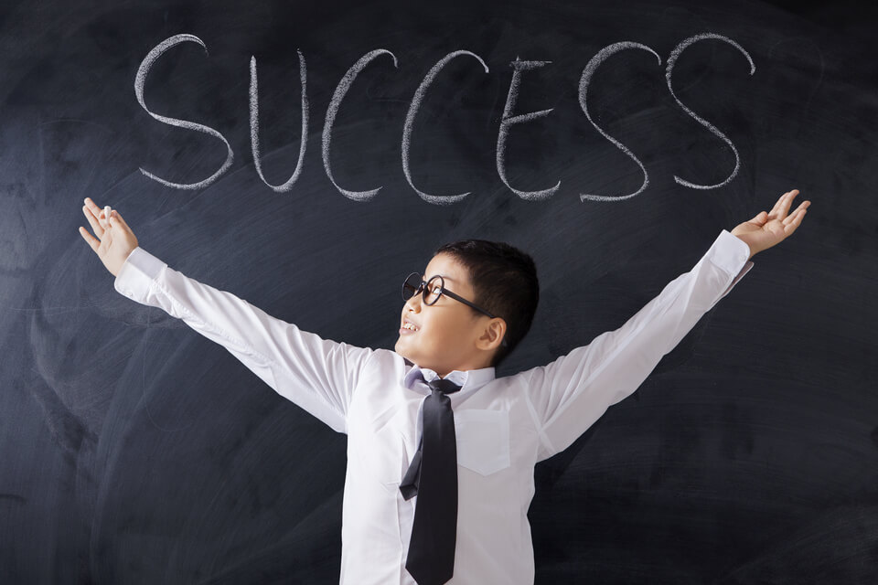 "happy boy in classroom with ""success"" written on blackboard"