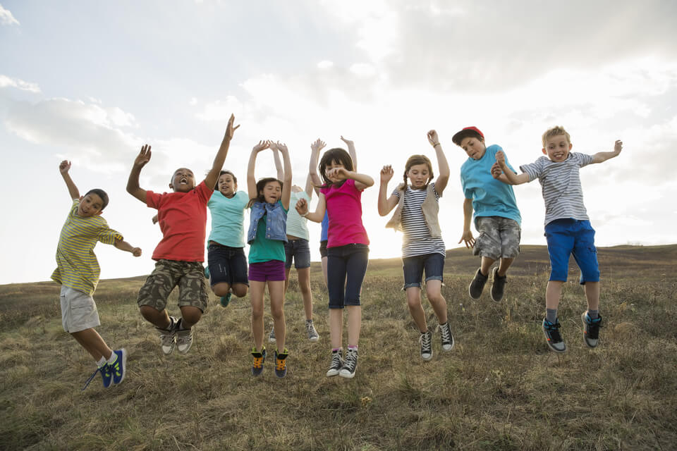 Group of kids jumping on hillside