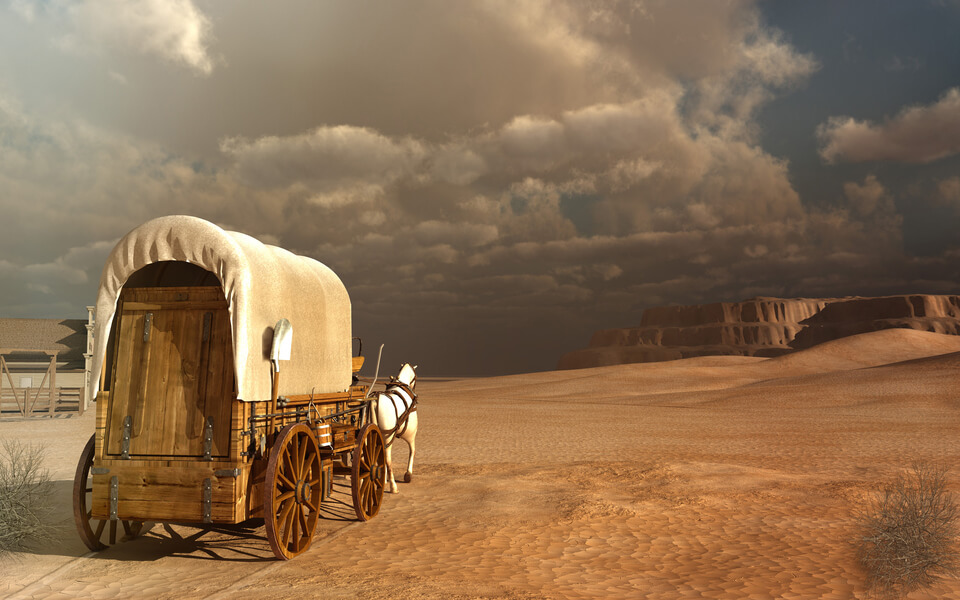 Desert landscape with old wagon and rocks