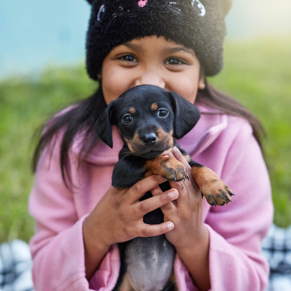 happy girl holding puppy