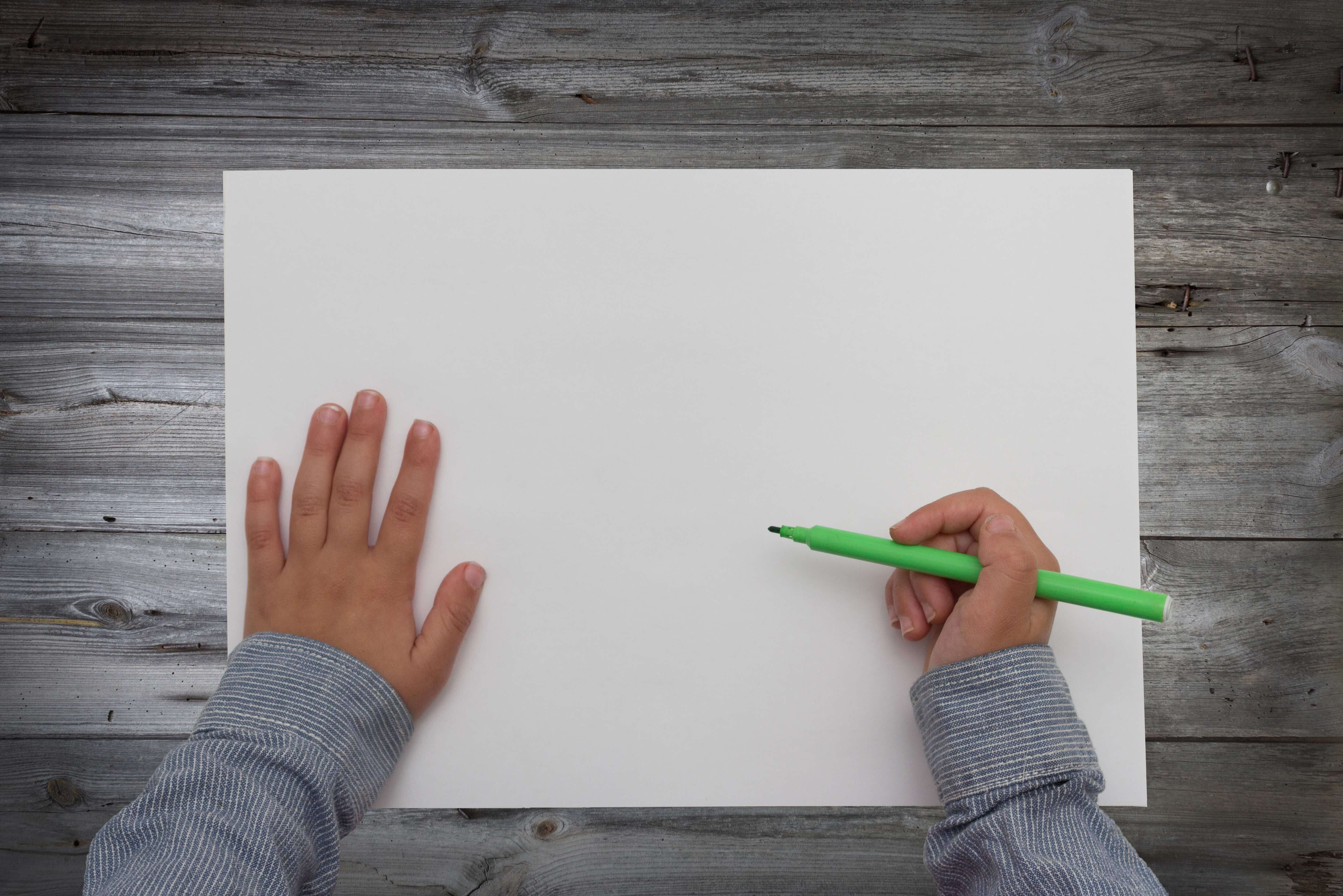 A child holds a marker over a blank piece of paper.