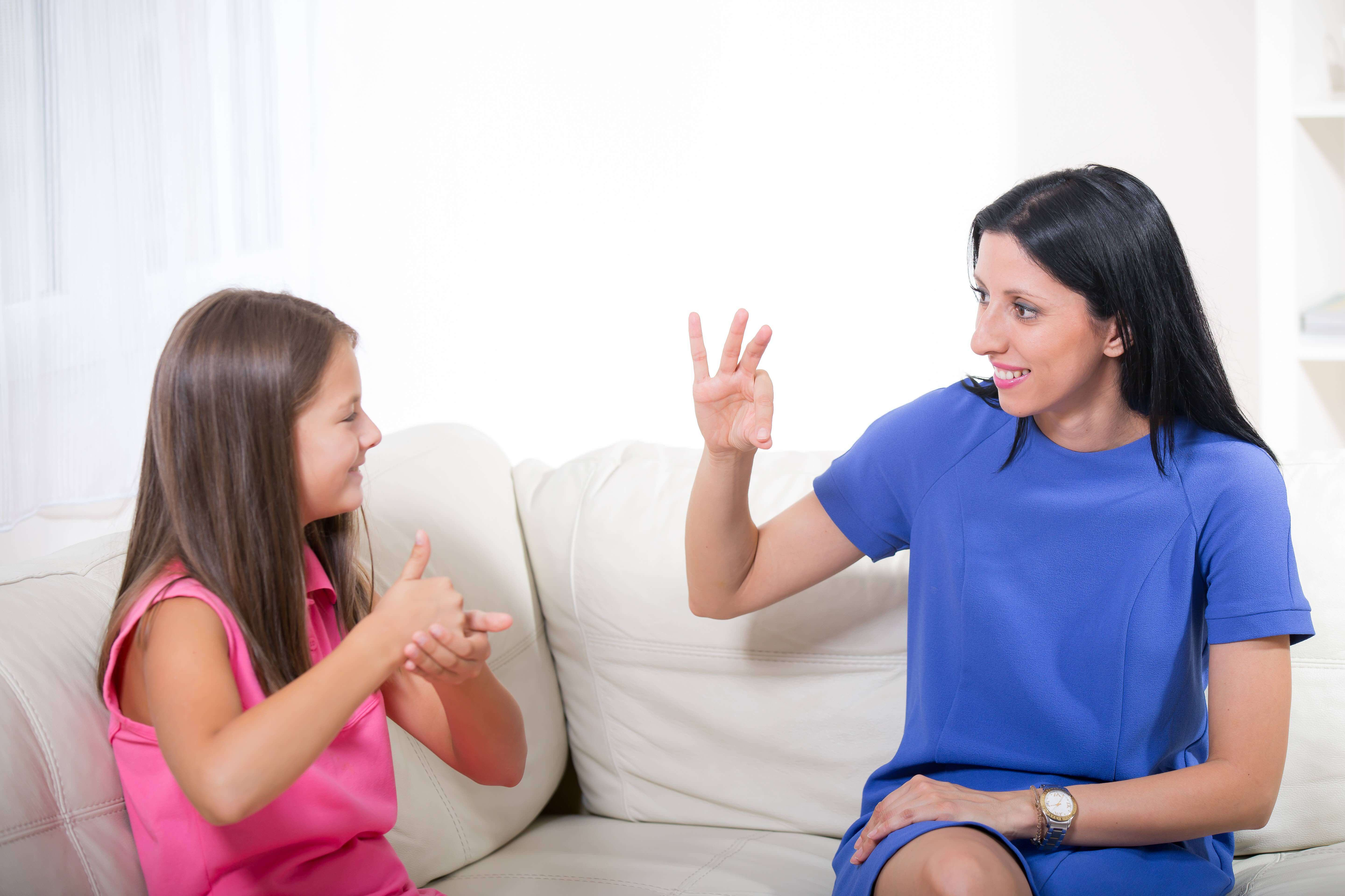 A girl uses sign language to communicate with a woman.