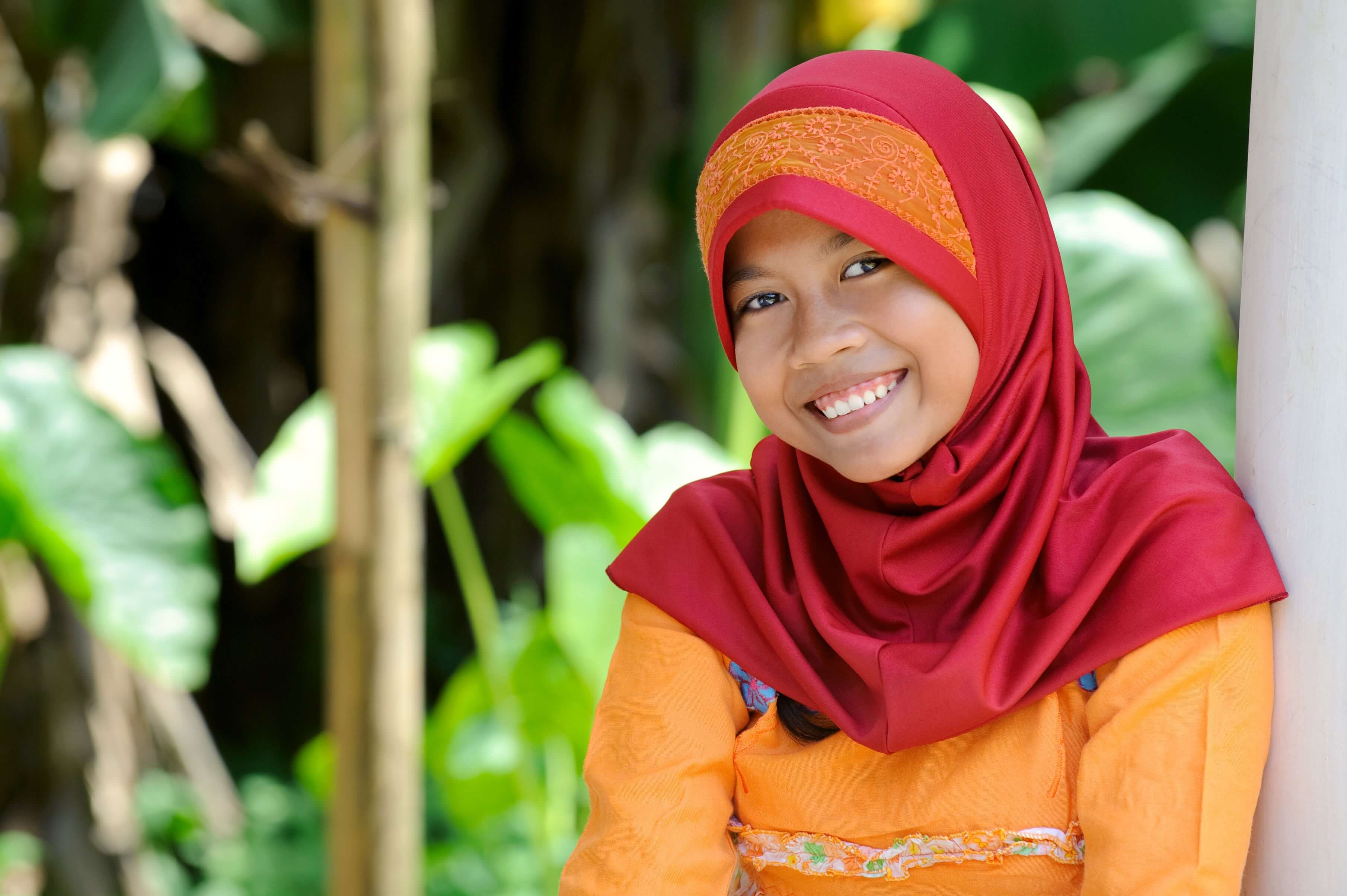 A girl poses with a wide smile.