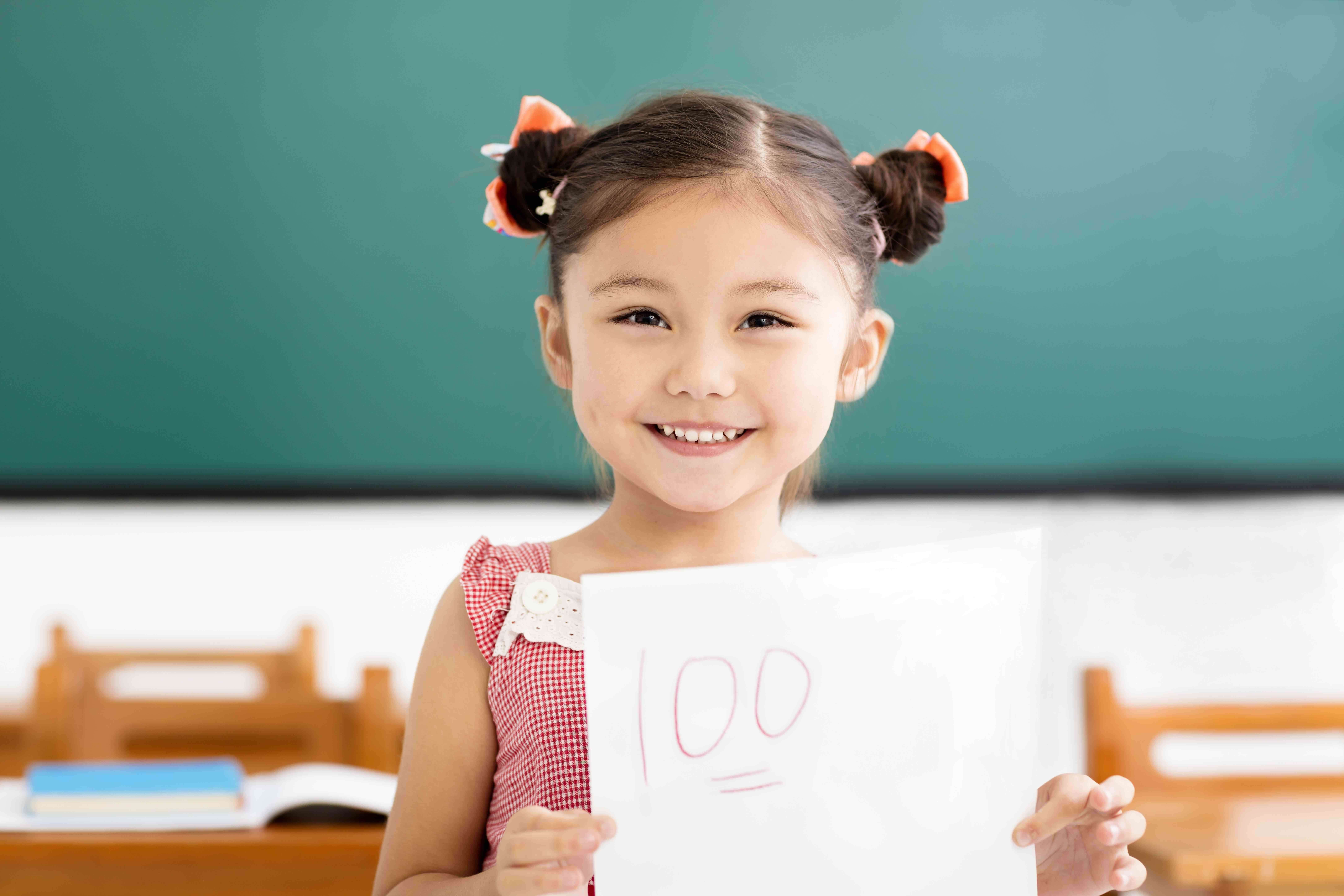 "A girl smiles and holds up a paper with the grade ""100"" written at the top."