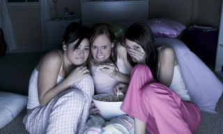 Three girls watching a scary show and eating popcorn