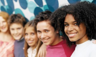 Group of smiling teenagers standing in front of a colorful background