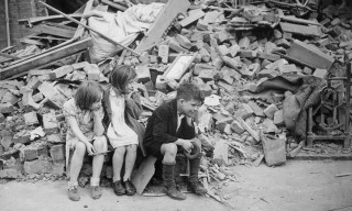 Children of an eastern suburb of London, who have been made homeless by the random bombs of the Nazi night raiders, waiting outside the wreckage of what was their home, World War II, 1940