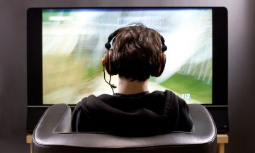 Teenager (15 years old) sitting in chair, shot from behind in studio playing video game on flat screen TV, New York, USA