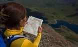 Over-the-shoulder shot of hiker reading map on mountainside