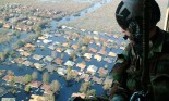 OVER NEW ORLEANS Tech. Sgt. Keith Berry looks down into flooded streets searching for survivors. He is part of an Air Force Reserve team credited with saving more than 1,040 people in the aftermath of Hurricane Katrina. He is a pararescueman with the 304th Rescue Squadron from Portland, OR. (U.S. Air Force photo by Master Sgt. Bill Huntington) No perm required. Photo 050904-F-8110H-033.