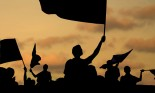 Silhouette of street protestors with flags and banners