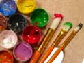 Paintbrushes and paint pots on wooden palette