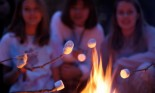 Three girls toasting marshmallows over a campfire