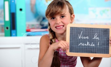 Elementary girl holding small slate, stating Vive la rentree! -- Back to School!