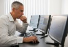 Businessman working at computer, hand resting on chin
