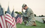 American soldier in uniform kneeling at grave on Memorial Day