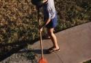 Boy sweeping sidewalk