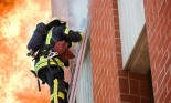 Firefighter on ladder with large flames in background