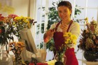 Florist cutting flowers in flower shop