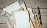 vintage notebook old papers and pens on a wooden table