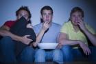 Three men watching a horror movie