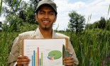 Researcher posing with graphs in wetland