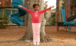Girl standing in front of tree in a playground, arms stretched wide