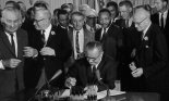 President Lyndon B. Johnson signs the 1964 Civil Rights Act as Martin Luther King, Jr. and others look on, East Room, White House, Washington, DC