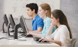 Three teenagers (16-17 years old) in computer laboratory