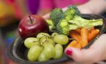 Student holding healthy plate of food in school cafeteria
