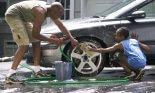 Father and son (10-11 years old) washing their car