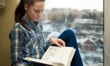 Girl sitting on a windowsill and reading a book