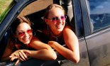 Two teenage girls wearing sunglasses leaning out of a car window.