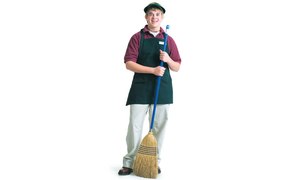 Teenage male grocery store employee stands with a broom