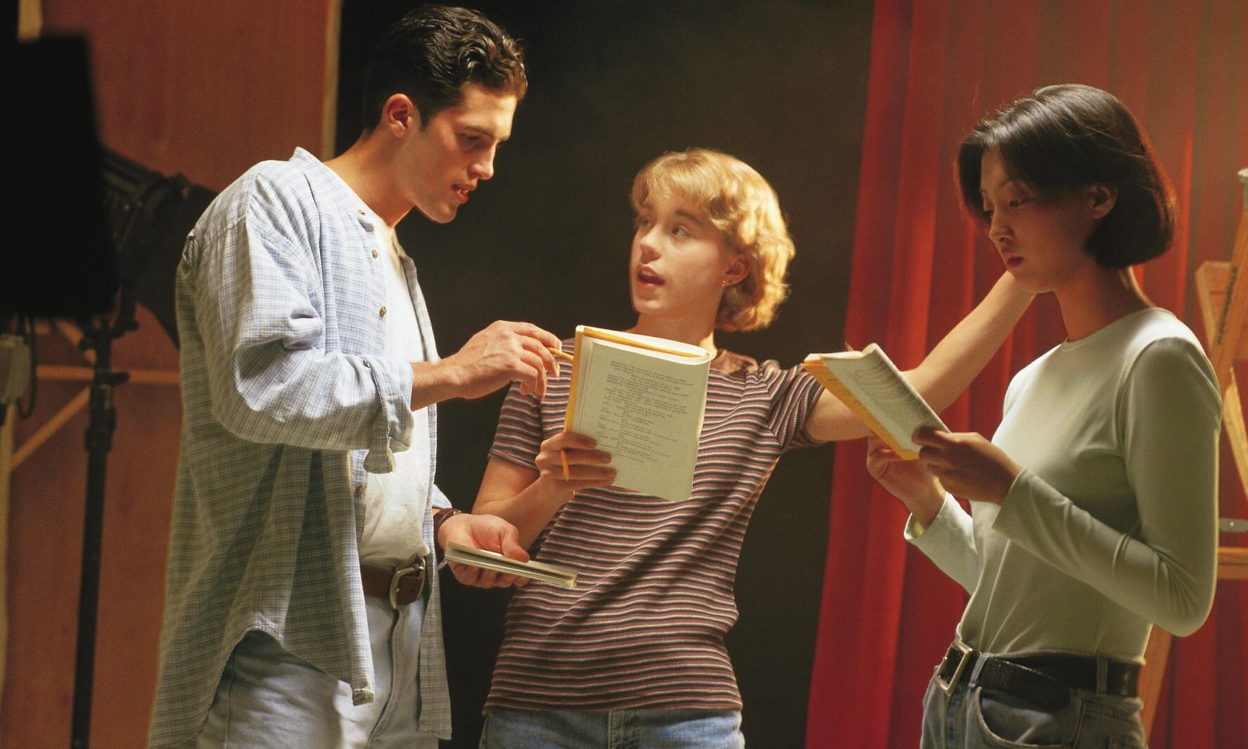 Three actors practicing their lines in a theater
