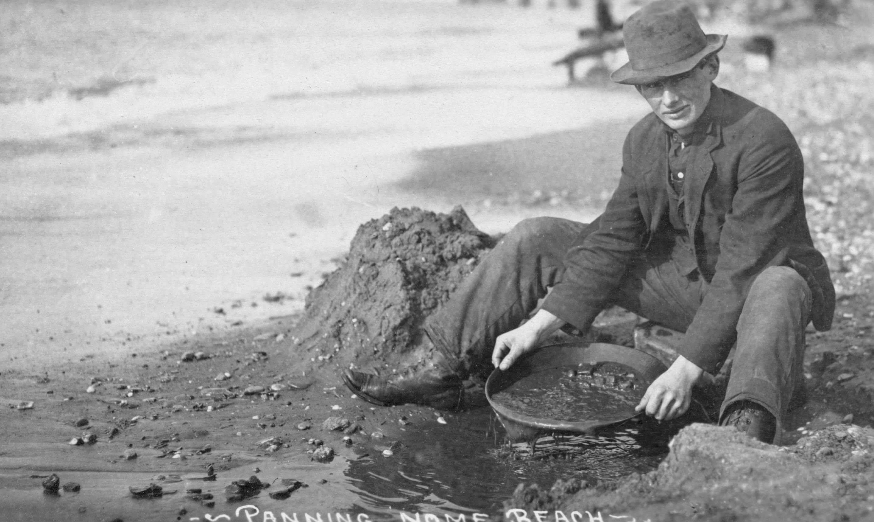 Man panning gold on Nome, Alaska, beach in the early 20th century