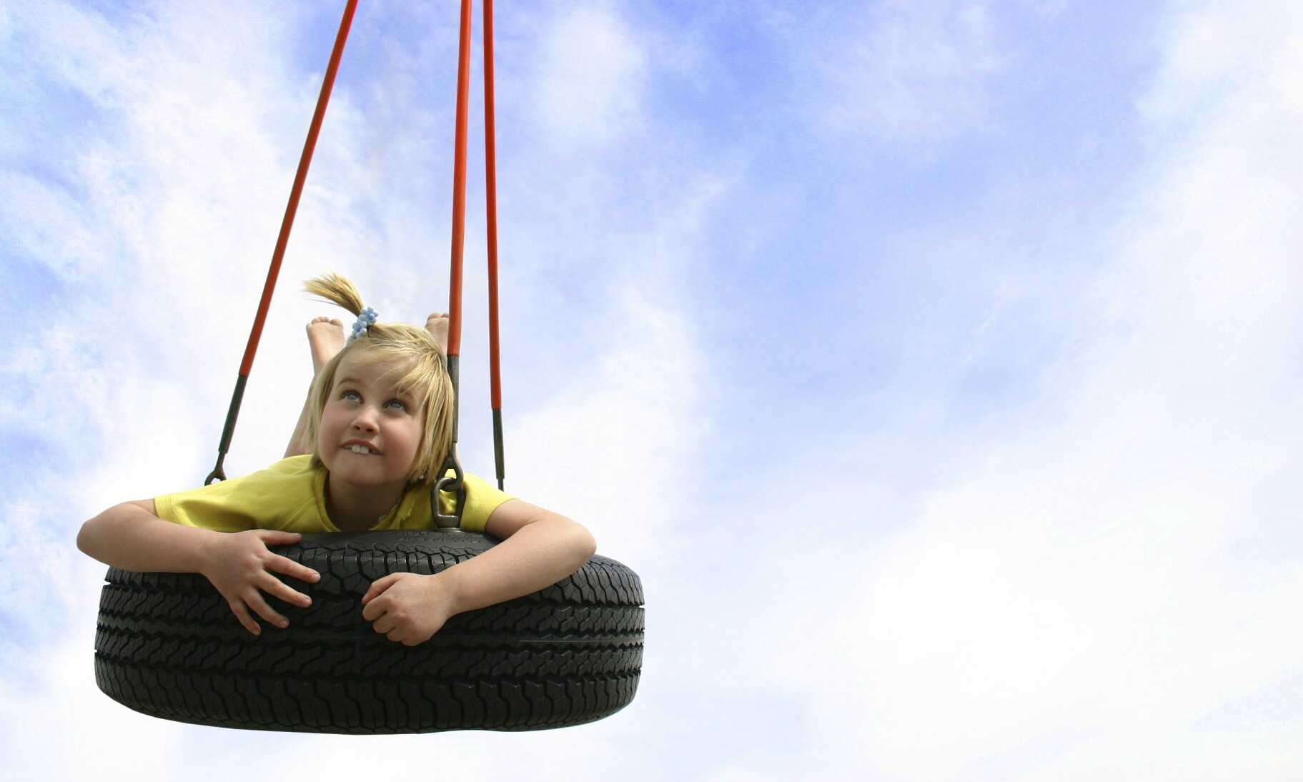 Girl swinging on a tire swing