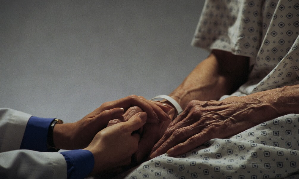 woman's hands holding an elderly person's hands