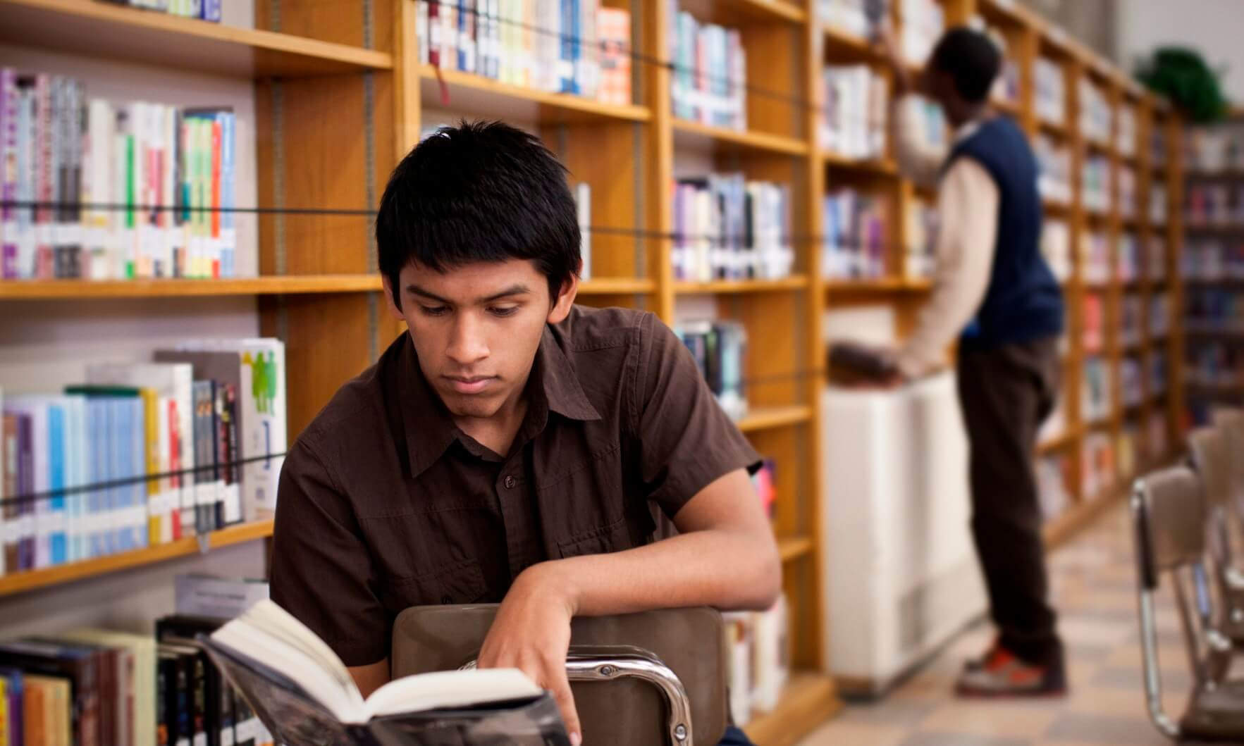 Teenage boy reading in school library