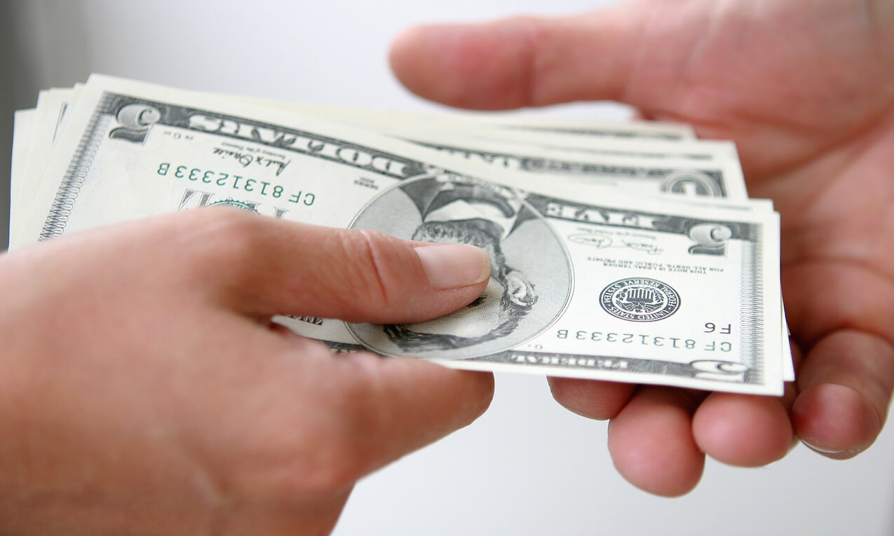 Two people exchanging money, close up of their hands